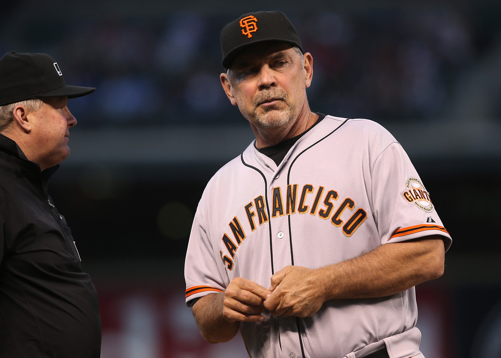 . San Francisco Giants manager Bruce Bochy, right, asks third base umpire Bill Miller for an replay to check ruling on hit by Tyler Colvin against the Colorado Rockies in the fifth inning of a baseball game in Denver on Tuesday, May 20, 2014. Colvin was awarded a double after the initial call was reviewed. (AP Photo/David Zalubowski)
