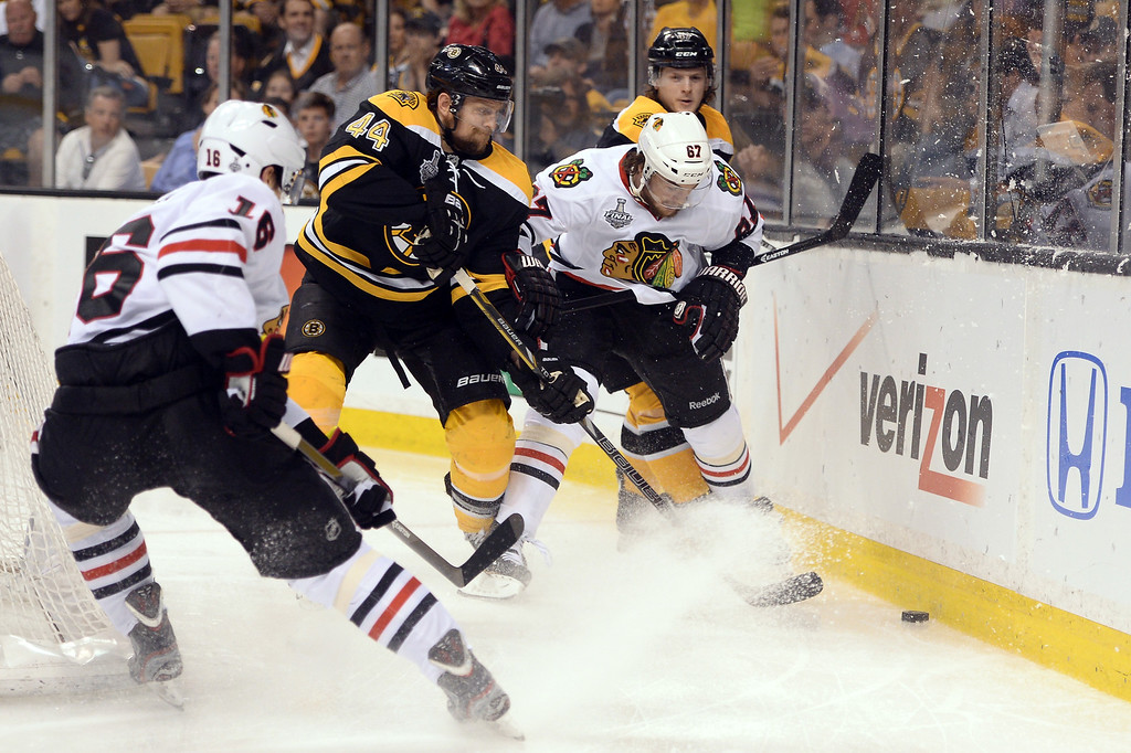 . Dennis Seidenberg #44 of the Boston Bruins fights for the puck with Michael Frolik #67 of the Chicago Blackhawks in Game Four of the 2013 NHL Stanley Cup Final at TD Garden on June 19, 2013 in Boston, Massachusetts.  (Photo by Harry How/Getty Images)