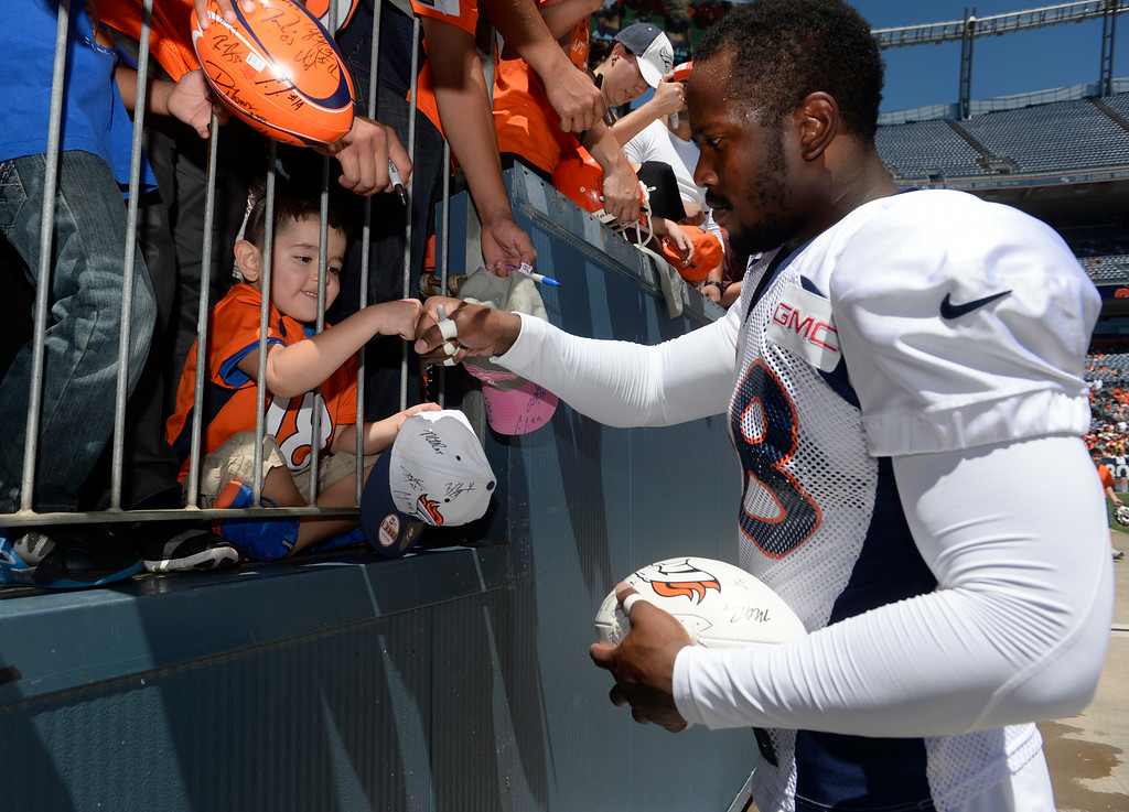 . Denver Broncos LB, Von Miller, fist bumps young fan, Romeo Ramirez, 4, after signing an autograph for him after practice and scrimmage at Sports Authority Field at Mile High Saturday afternoon, August 02, 2014. (Photo By Andy Cross / The Denver Post)