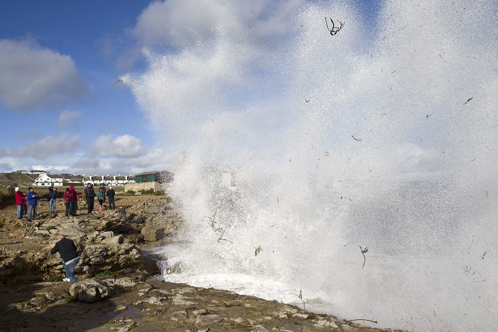 . People react as they watch a jet of sea water being propelled into the air in Portland Bill in Dorest in southern England on October 28, 2013 following a strong storm.  AFP PHOTO / JUSTIN TALLIS/AFP/Getty Images
