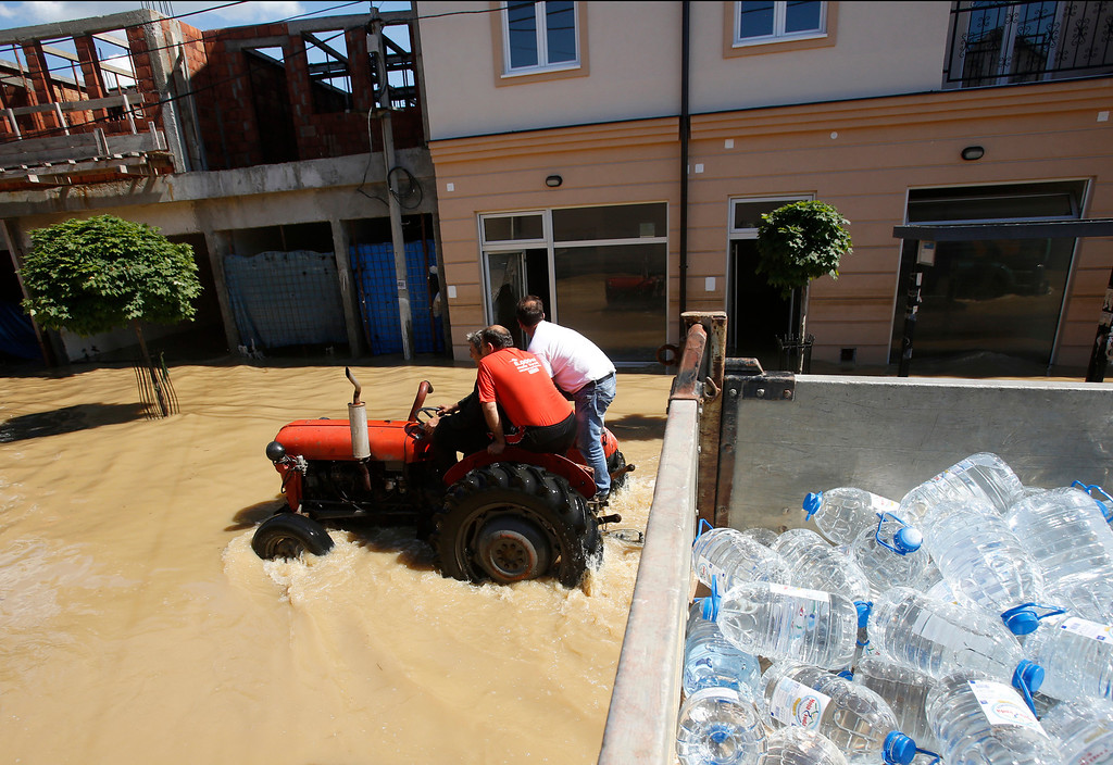 . People ride on tractor in a flooded street in Obrenovac, some 30 kilometers (18 miles) southwest of Belgrade, Serbia, Monday, May 19, 2014. Belgrade braced for a river surge Monday that threatened to inundate Serbia\'s main power plant and cause major power cuts in the crisis-stricken country as the Balkans struggle with the consequences of the worst flooding in southeastern Europe in more than a century.  (AP Photo/Darko Vojinovic)