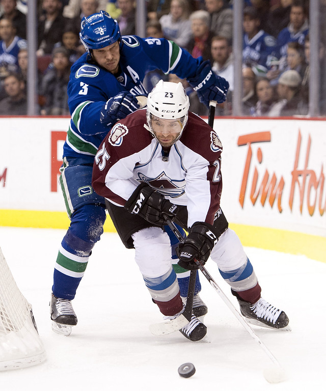 . Kevin Bieksa #3 of the Vancouver Canucks gets his stick caught between the legs of Max Talbot #25 of the Colorado Avalanche during the first period in NHL action on December 08, 2013 at Rogers Arena in Vancouver, British Columbia, Canada. Bieksa received a minor penalty on the play.  (Photo by Rich Lam/Getty Images)
