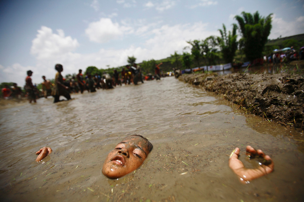 . A boy enjoys lying down on mud while celebrating Asar Pandhra festival in Pokhara valley, west of Nepal\'s capital Kathmandu June 29, 2012. Farmers in Nepal celebrate the festival to mark the commencement of rice crop planting in paddy fields. REUTERS/Navesh Chitrakar