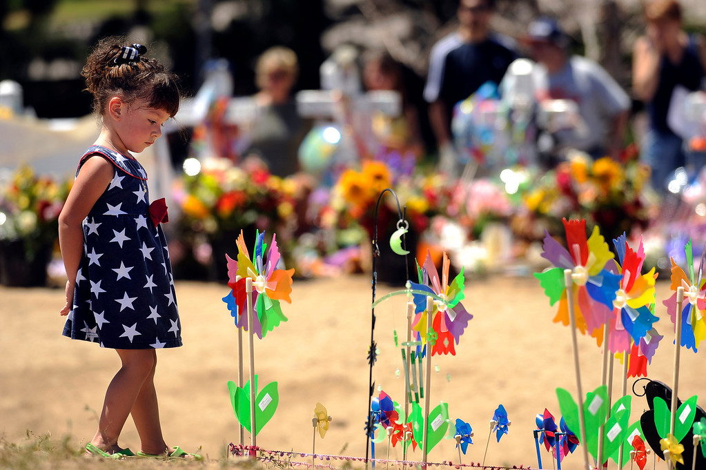 . Lilly Francis, 2, of Northglenn stops by Aurora\'s Wind Farm at the memorial for shooting victims in Aurora, Colo. Saturday, July 28, 2012. Hyoung Chang, The Denver Post