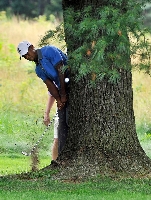 . Tiger Woods hits to the fairway from behind a tree on the sixth hole during the second round at the WGC Bridgestone Invitational golf tournament, at Firestone Country Club in Akron, Ohio, Friday, Aug. 2,  2013. (AP Photo/Phil Long)