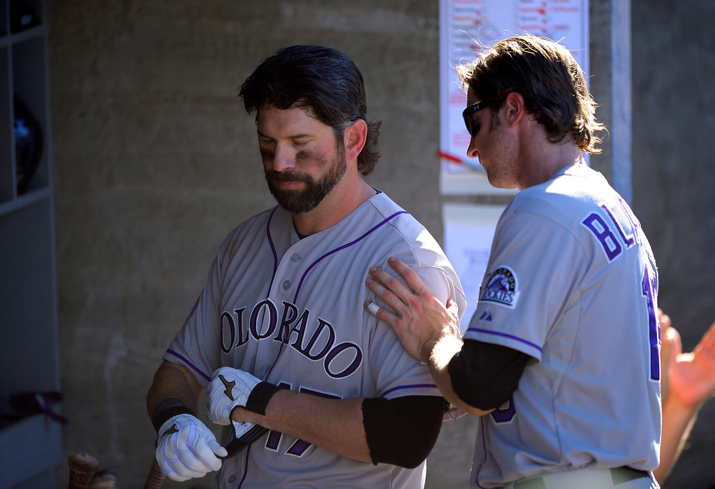 . Colorado Rockies\' Todd Helton, left, gets a pat from Charlie Blackmon after striking out in the ninth inning of the Rockies\' baseball game against the Los Angeles Dodgers, Sunday, Sept. 29, 2013, in Los Angeles.  (AP Photo/Mark J. Terrill)
