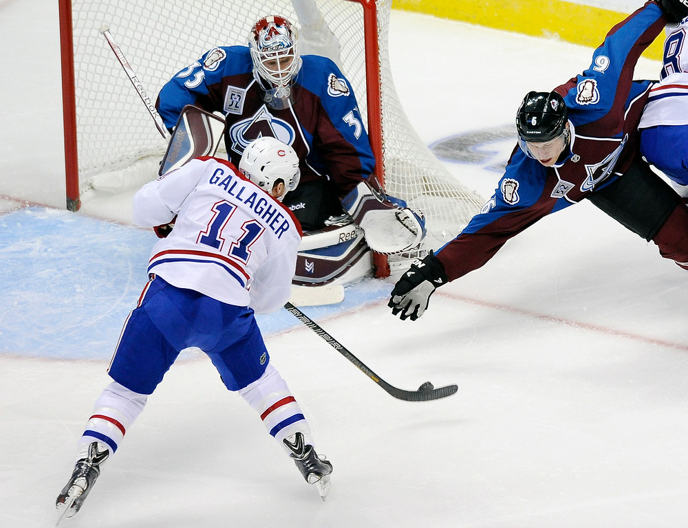 . Colorado Avalanche defenseman Erik Johnson, right, tries to block a shot by Montreal Canadiens right wing Brendan Gallagher, left, against Avalanche goalie Jean-Sebastien Giguere, top center, in the first period of an NHL hockey game on Saturday, Nov. 2, 2013, in Denver. The Avalanche won 4-1. (AP Photo/Chris Schneider)