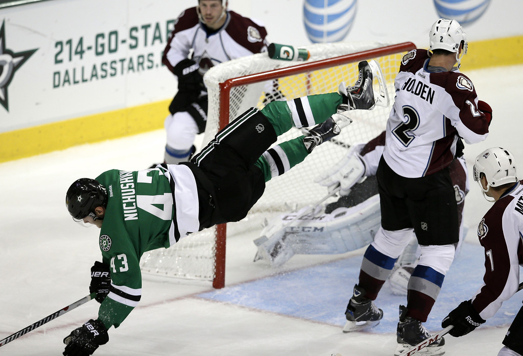 . Dallas Stars\' Valeri Nichushkin (43), of Russia, is sent flying after scoring a goal against Colorado Avalanche goalie Semyon Varlamov (1), also of Russia, as Matt Hunwick, left rear, Nick Holden (2) and John Mitchell (7) watch in the third period of a preseason NHL hockey game on Thursday, Sept. 26, 2013, in Dallas. The Stars won 5-1. (AP Photo/Tony Gutierrez)