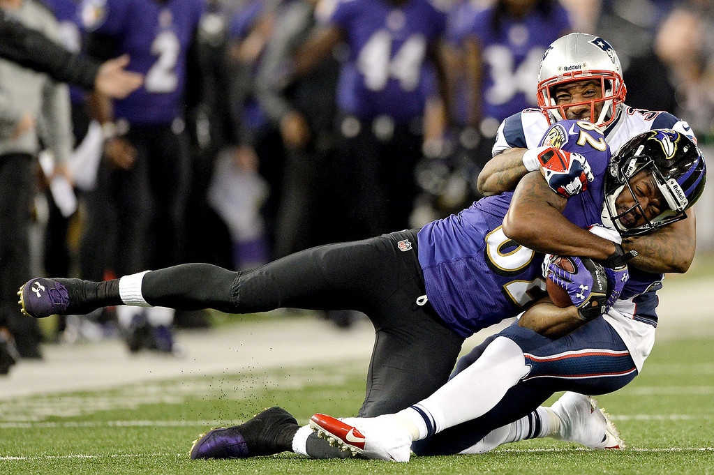 . Wide receiver Torrey Smith #82 of the Baltimore Ravens is tackled by cornerback Aqib Talib #31 of the New England Patriots in the third quarter at M&T Bank Stadium on December 22, 2013 in Baltimore, Maryland. The New England Patriots won, 41-7. (Photo by Patrick Smith/Getty Images)