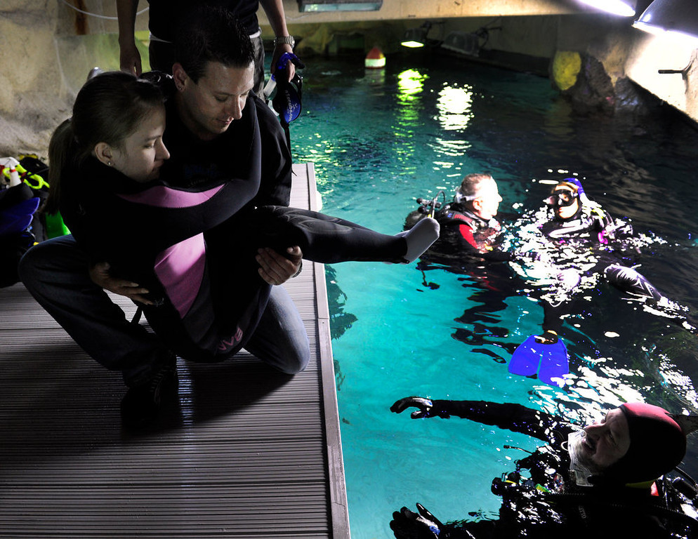 . DENVER, CO. - FEBRUARY 16: With dive instructor Scott Taylor ready to help, instructor Shane Taylor lowers Brittney Martin,18, who has spina bifida, down to the water for her dive. Two teens from the Riley Children\'s Foundation are learning how to scuba dive with instructors from the A-1 Scuba and Travel Aquatics Center at the Downtown Aquarium.(Photo By Kathryn Scott Osler/The Denver Post)