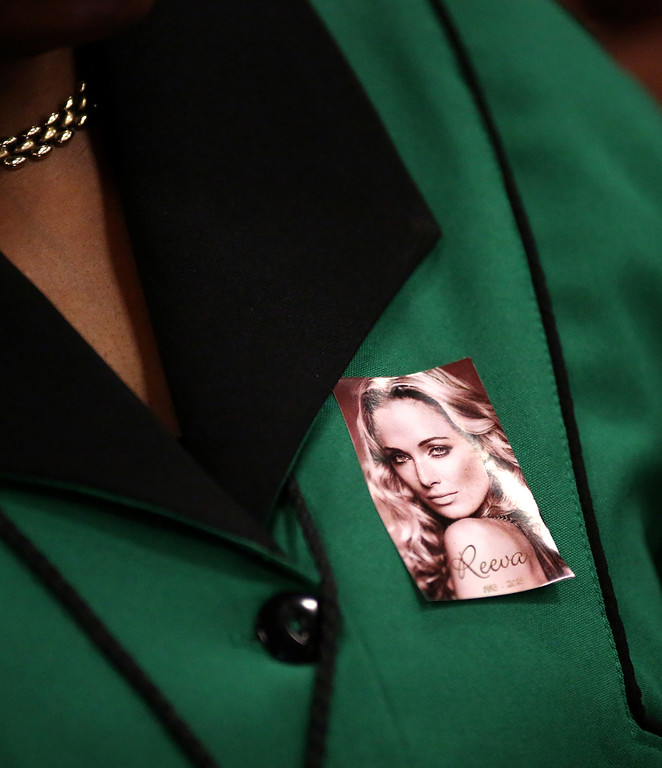. A member of the African National Congress Womens League wears a photo of the late Reeva Steenkamp, girlfriend of Oscar Pistroius, pinned to her top as she attends court on the third day of Pistorius\' trial at the high court in Pretoria, South Africa, Wednesday, March 5, 2014. Pistorius is charged with murder for the shooting death of his girlfriend, Reeva Steenkamp, on Valentines Day in 2013. (AP Photo/Mike Hutchings-Pool)