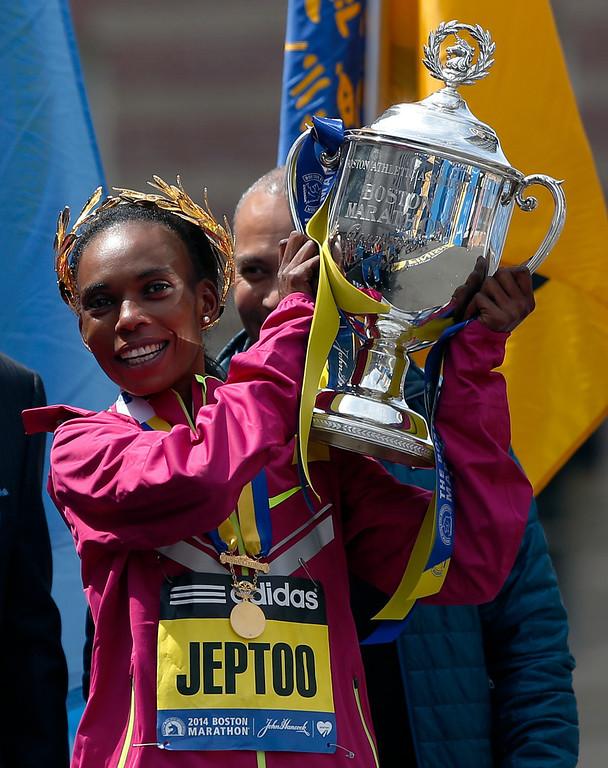 . Rita Jeptoo, of Kenya, hoists the trophy after winning the women\'s division of the 118th Boston Marathon Monday, April 21, 2014 in Boston. (AP Photo/Elise Amendola)