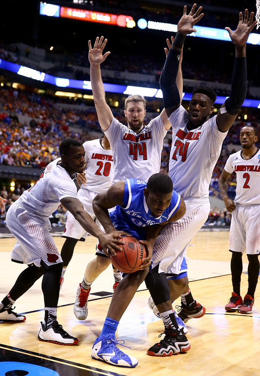 . Alex Poythress #22 of the Kentucky Wildcats is defended by Chris Jones #3 and Montrezl Harrell #24 and Stephan Van Treese #44 of the Louisville Cardinals during the regional semifinal of the 2014 NCAA Men\'s Basketball Tournament at Lucas Oil Stadium on March 28, 2014 in Indianapolis, Indiana.  (Photo by Andy Lyons/Getty Images)