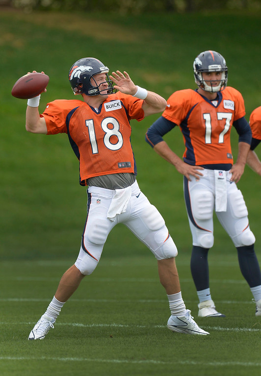 . Denver Broncos quarterback Peyton Manning (18) throws a pass downfield as Denver Broncos quarterback Brock Osweiler (17) watches during practice September 1, 2013 at Dove Valley. (Photo by John Leyba/The Denver Post)