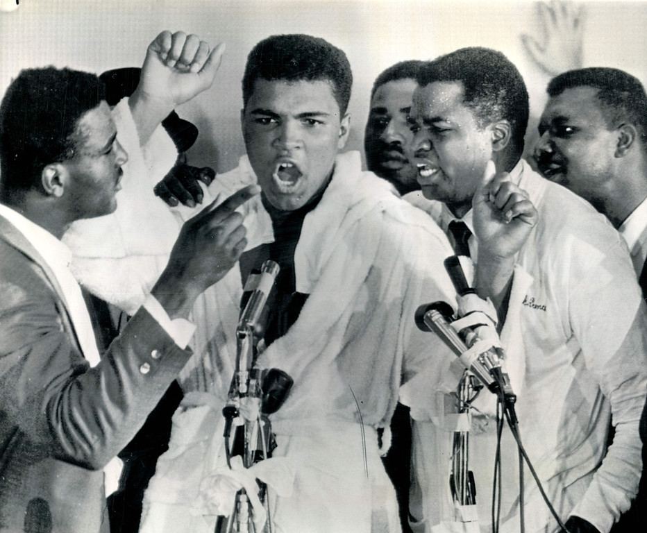 . MIAMI BEACH, Fla., Feb. 25, 1964--THE LIP HAS HIS SAY--Never for a loss of words, Cassius Clay answers questions during news conference after his technical knockout win over world heavyweight champ Sonny Liston in Miami Beach, Fla.  At Clay\'s left is a handler, Drew Brown.    Credit: AP