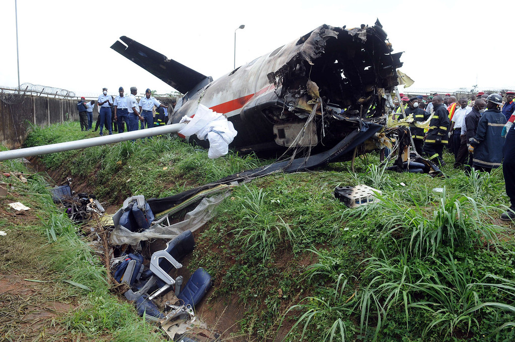 . Nigerian rescue workers gather around the wreckage of an Associated Airlines plane that crash-landed at Sahara Airport shortly after takeoff in Lagos on October 3, 2013. The Nigerian charter plane with 27 people on board suffered engine failure shortly after takeoff from Lagos, crash-landing near an airport fuel depot and killing at least nine people, officials said. AFP PHOTO/ PIUS UTOMI EKPEI/AFP/Getty Images