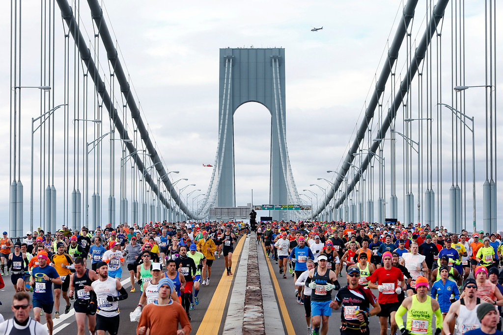 . Police and U.S. Coast Guard helicopters fly overhead as runners cross the Verrazano-Narrows Bridge at the start of the New York City Marathon, Sunday, Nov. 3, 2013, in New York. (AP Photo/Jason DeCrow)