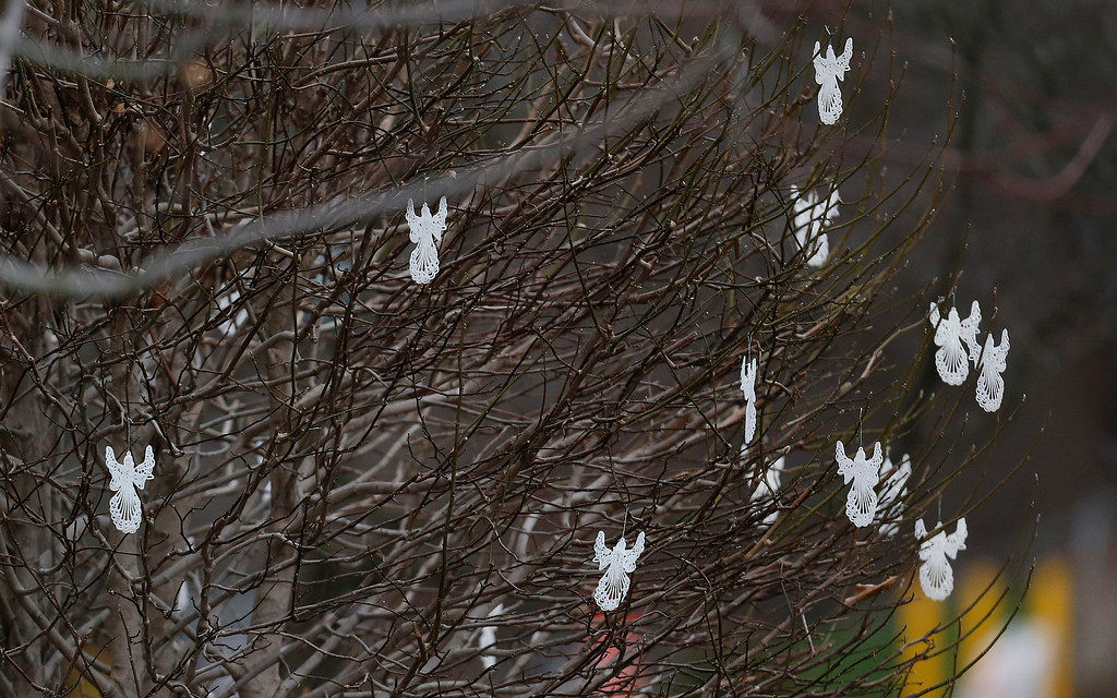 . Angles dangle from a tree in front of St. Rose of Lima Roman Catholic Church before Mass, on Sunday, Dec. 16, 2012, in Newtown, Conn. A gunman walked into Sandy Hook Elementary School in Newtown Friday and opened fire, killing 26 people, including 20 children. (AP Photo/Julio Cortez)
