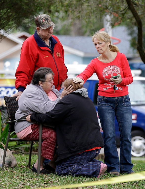 . Family members console each other near the home where Jeff Bush disappeared as a large sinkhole opened under the bedroom of his house on  Friday, March 1, 2013, in Seffner, Fla.  (AP Photo/Chris O\'Meara)