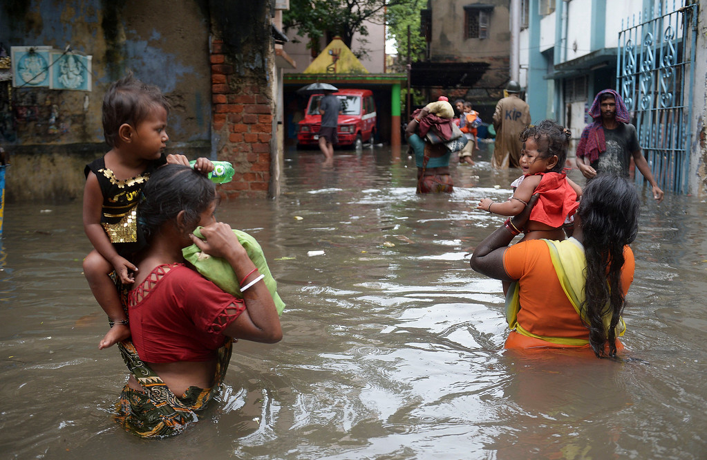 . An Indian Police official guides pavement dwellers through water-logged streets to a to a safer place in Kolkata on October 26, 2013.  Persistent rain for the last 24 hours has thrown normal life in this metropolis out of gear with reports of waterlogging at major arterial roads of the city which received 14 cm rainfall, the highest rainfall during the ongoing depression in eastern India.  Weathermen predicted that the rain, caused due to a depression off Andhra coast over Bay of Bengal, would continue for at least next 24 hours. DIBYANGSHU SARKAR/AFP/Getty Images