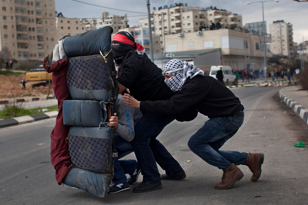. Masked Palestinians use a back car seat as a shield during a protest to support Palestinian prisoners, outside Ofer, an Israeli military prison near the West Bank city of Ramallah, Tuesday, Feb. 19, 2013. Palestinian protesters clashed with Israeli soldiers at a rally in support of four imprisoned Palestinians on hunger strike, as hundreds of inmates said they were refusing food for the day in solidarity with the fasting inmates. One of the four hunger-striking Palestinians is 35-year-old Samer Issawi whose health has severely deteriorated after he has refused food, on-and-off, for more than 200 days. (AP Photo/Bernat Armangue, File)