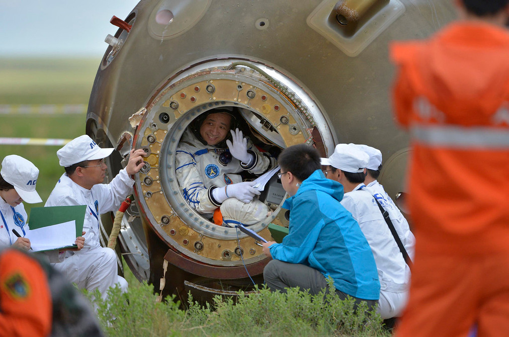 . Chinese astronaut Nie Haisheng waves before getting out of the re-entry capsule of China\'s Shenzhou-10 spacecraft after it landed at its main landing site in Inner Mongolia Autonomous Region, June 26, 2013. Three Chinese astronauts returned to Earth on Wednesday, touching down in north China\'s Inner Mongolia after a successful 15-day mission in which they docked with a manned space laboratory.  REUTERS/China Daily