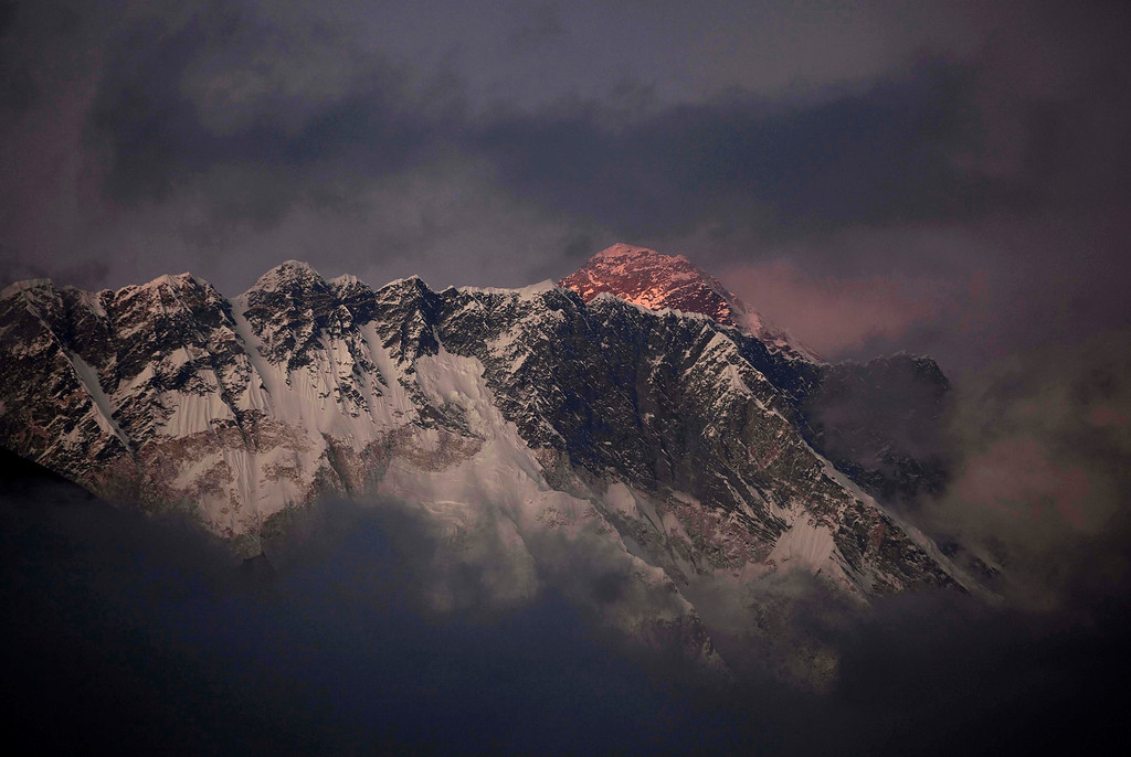 . FILE - In this Oct. 27, 2011 file photo, the last light of the day sets on Mount Everest as it rises behind Mount Nuptse as seen from Tengboche, in the Himalaya\'s Khumbu region, Nepal. An avalanche swept the slopes of Mount Everest on Friday, April 18, 2014, along a route used to ascend the world\'s highest peak, killing at least six Nepalese guides and leaving nine more missing, officials said. (AP Photo/Kevin Frayer, File)