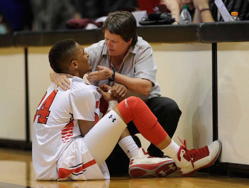 . BOULDER, CO. - MARCH 15: East guard Dominique Collier showed his teeth to trainer Lisa Smith after he smashed his face on the court in the fourth quarter. The East High School boy\'s basketball team defeated Legend 58-45 Friday night, March 15, 2013 at the Coors Events Center in a 5A semifinal playoff game.  (Photo By Karl Gehring/The Denver Post)