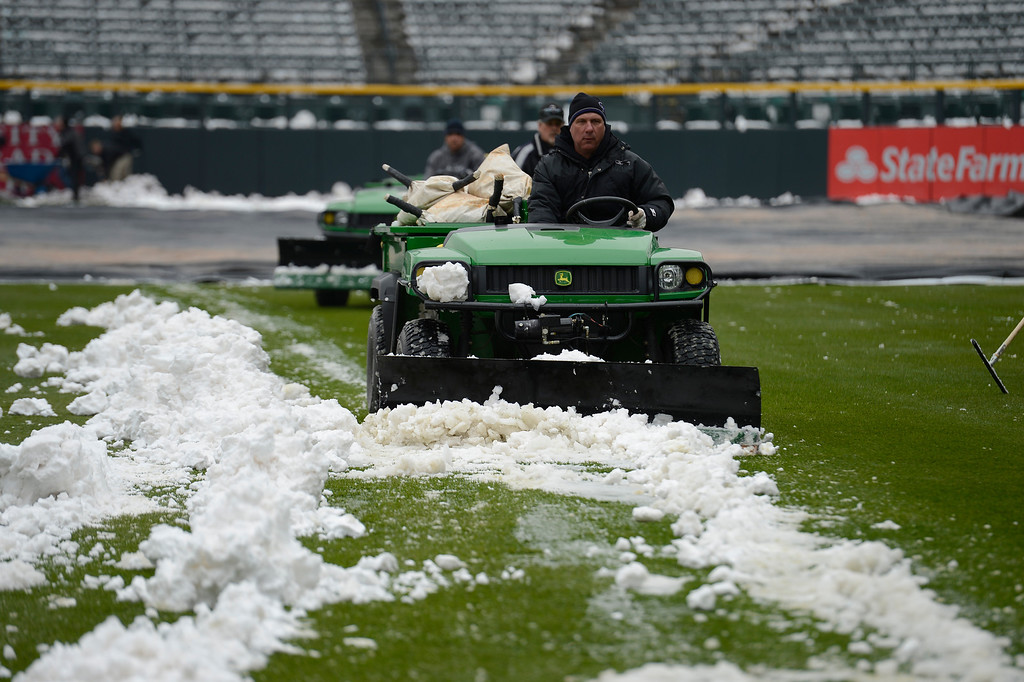 . Mark Razum runs the gator to clear snow off the right field grass after an overnight storm hit the area. Rockies grounds crew and employees work to clear the field of snow to get the first game of a double header in against the  New York Mets April 16, 2013 at Coors Field. (Photo By John Leyba/The Denver Post)