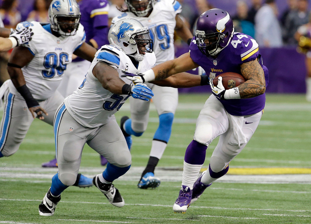 . Minnesota Vikings running back Matt Asiata, right, tries to break a tackle by Detroit Lions middle linebacker Stephen Tulloch during the first half of an NFL football game, Sunday, Dec. 29, 2013, in Minneapolis. (AP Photo/Ann Heisenfelt)