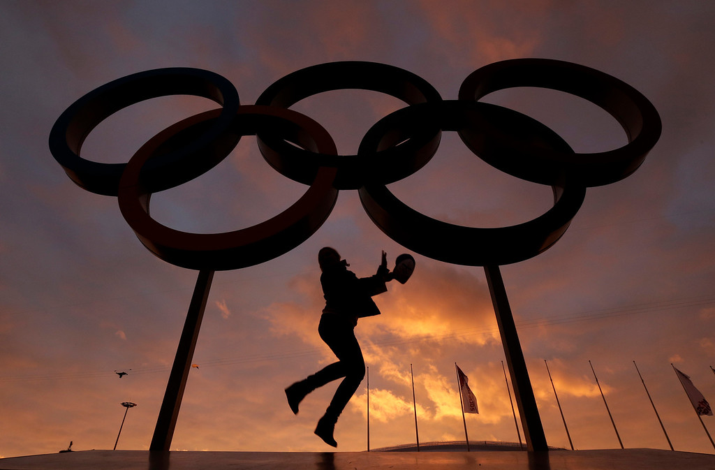 . A woman poses for with the Olympic rings in Olympic Park as preparations continue for the 2014 Winter Olympics, Wednesday, Feb. 5, 2014, in Sochi, Russia. (AP Photo/Charlie Riedel)