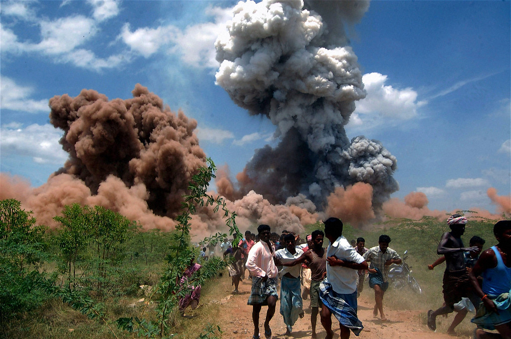 . In this Sept. 5, 2012 file photo, people run for cover as smoke rises from the site of a fire at a fireworks factory on the outskirts of Sivakasi, about 500 kilometers (310 miles) southwest of Chennai, India.  Police in southern India arrested six employees of the fireworks factory for a massive blaze that killed 40 workers and injured 60 others. (AP Photo, File) INDIA OUT