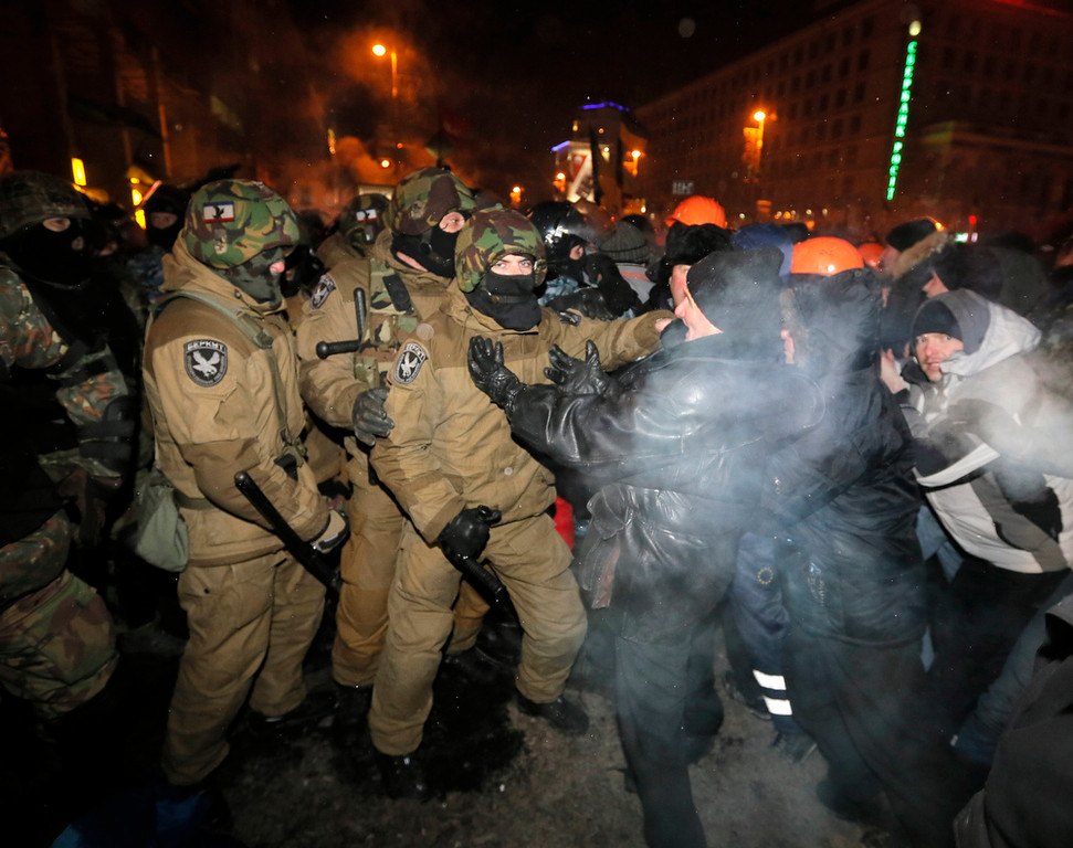 . Ukrainian riot police pull pro-European Union activists out from their camp on Independence Square in Kiev, Ukraine, Wednesday, Dec. 11, 2013. Security forces clashed with protesters as they began tearing down opposition barricades and tents set up in the center of the Ukrainian capital early Wednesday, in an escalation of the weeks-long standoff threatening the leadership of President Viktor Yanukovych.  (AP Photo/Efrem Lukatsky)