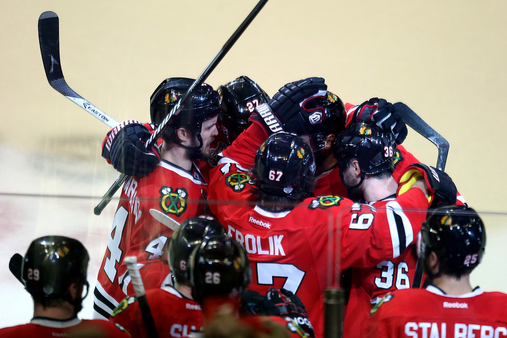 . CHICAGO, IL - JUNE 22:  Niklas Hjalmarsson #4, Michael Frolik #67 and Dave Bolland #36 of the Chicago Blackhawks celebrate after defeating the Boston Bruins in Game Five of the 2013 NHL Stanley Cup Final at United Center on June 22, 2013 in Chicago, Illinois.  The Chicago Blackhawks defeated the Boston Bruins 3-1.  (Photo by Jonathan Daniel/Getty Images)