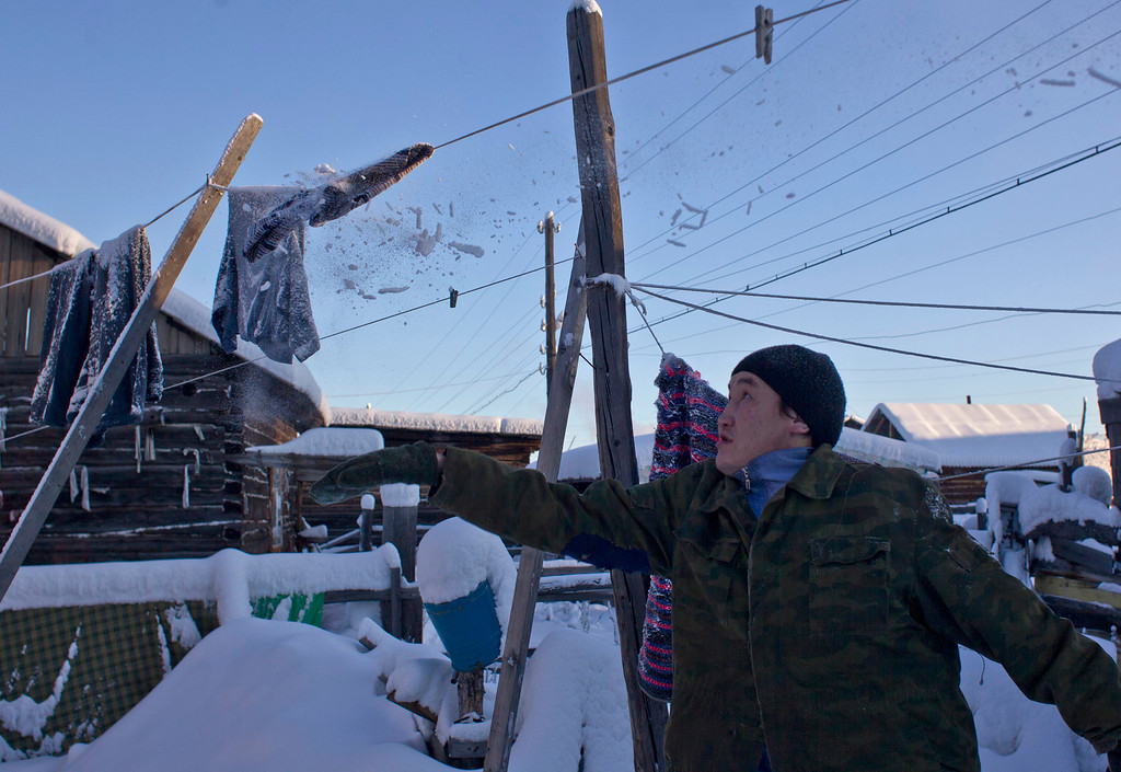 . Igor Vinokurov, 35, knocks snow and ice off a frozen washing line in the village of Oymyakon, in the Republic of Sakha, northeast Russia, January 26, 2013. The coldest temperatures in the northern hemisphere have been recorded in Sakha, the location of the Oymyakon valley, where according to the United Kingdom Met Office a temperature of -67.8 degrees Celsius (-90 degrees Fahrenheit) was registered in 1933 - the coldest on record in the northern hemisphere since the beginning of the 20th century. Yet despite the harsh climate, people live in the valley, and the area is equipped with schools, a post office, a bank, and even an airport runway (albeit open only in the summer).    Picture taken January 26, 2013.    REUTERS/Maxim Shemetov