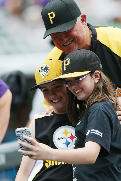 . Two young fans of the Pittsburgh Pirates take a photo with Pirates manager Clint Hurdle before the Colorado Rockies hosted Pittsburgh in the first inning of a baseball game in Denver, Sunday, July 27, 2014. (AP Photo/David Zalubowski)