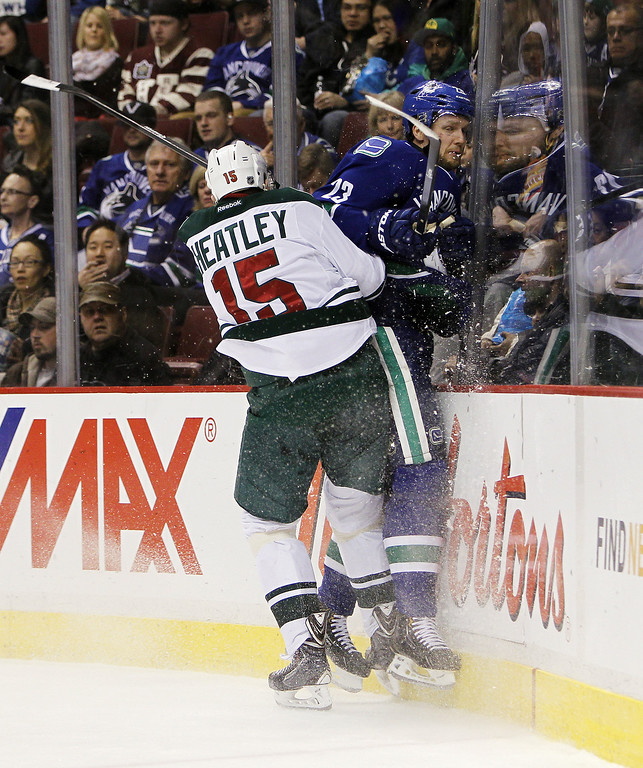 . Dany Heatley #15 of the Minnesota Wild collides with Alexander Edler #23 of the Vancouver Canucks during the first period of their NHL game at Rogers Arena on February 28, 2014 in Vancouver, British Columbia, Canada. (Photo by Ben Nelms/Getty Images)