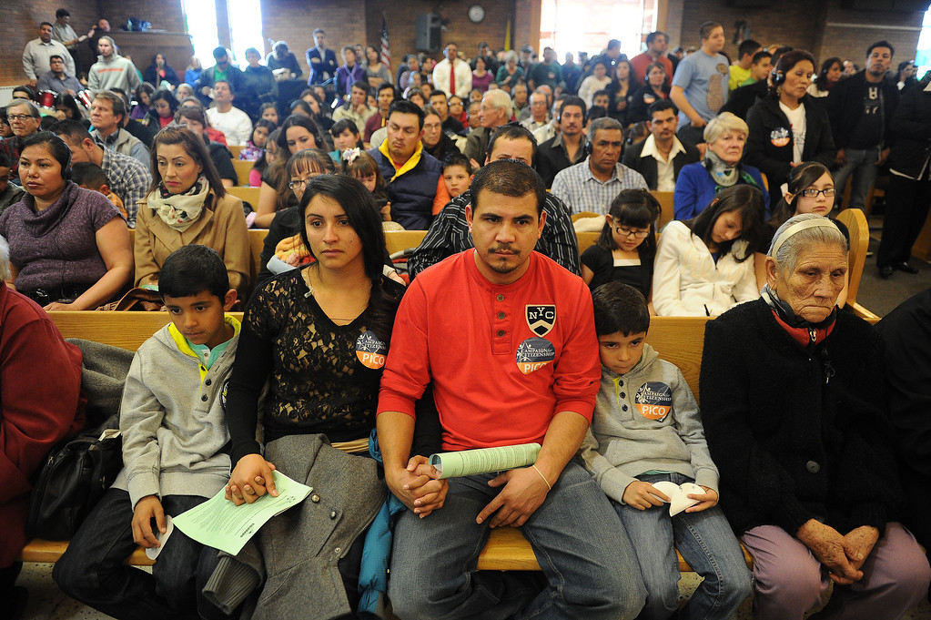 . AURORA, CO- FEBRUARY 9:  Juan Renteria and his wife Melissa Maciel hold hands with their children Brandon Renteria, 6, right and Bryan, 9, left during the meeting.  TOGETHER COLORADO held a public meeting  to talk about the United States immigration policies at St. Therese Catholic Church, 1243 Kingston Street in Aurora, Co  on February 9th, 2013.   Colorado State Senator Michael Bennet, and Colorado Representatives Mike Coffman and Jared Polis attended and spoke at the meeting.  The organization wanted to tell the state\'s representatives why they want a road map to citizenship for 11 million aspiring Americans.  More than 800 faith and community leaders packed the small church in Aurora. (Photo By Helen H. Richardson/ The Denver Post)