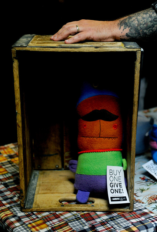 ". Ray Tollison rests his hand on a case that houses one of his monsters on Dec. 6 at the Holiday Mancraft 2013 craft fair at the VFW Post in Denver, Colo. ""A Monster to Love\"" was created by Tollison and his 12-year-old twin boys, who help design and sew the monsters. Photo by Jamie Cotten, Special to The Denver Post"