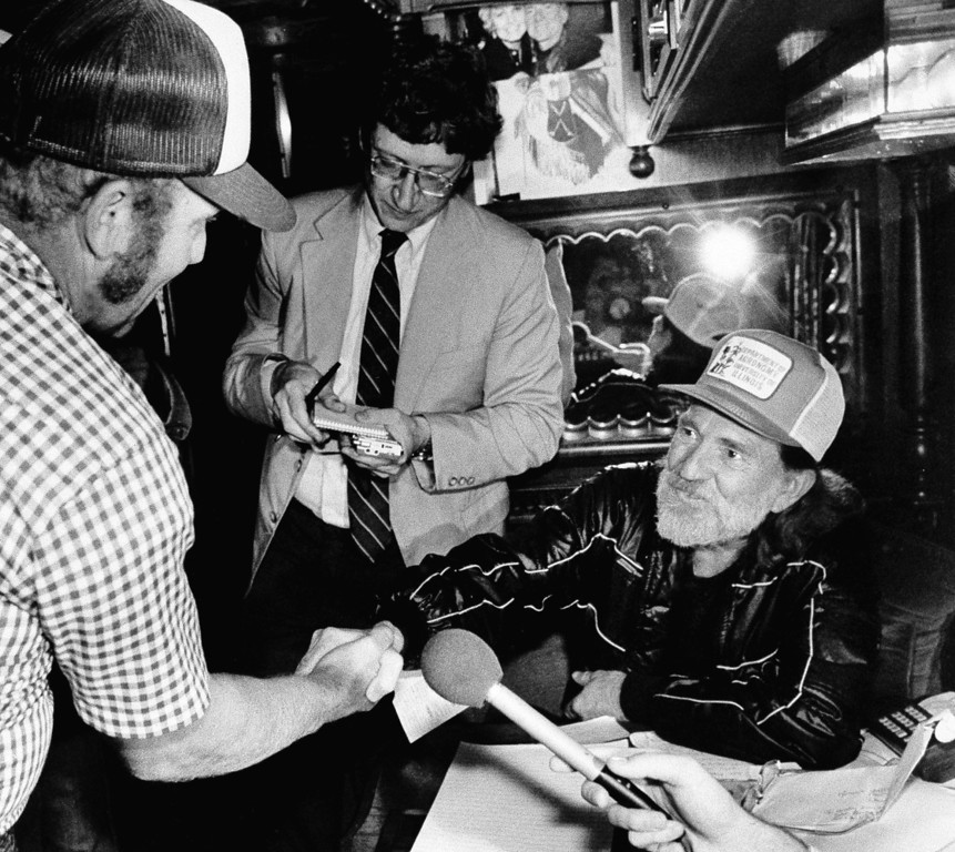 . Country-western singer Willie Nelson, right, shakes hands with farmer Marvin Espenscheid Friday August 23, 1985  who Nelson invited onto his bus to discuss farm problems at the Minnesota State Fair.   Nelson was to have toured the cattle barn to talk with farmers, but the large crowd forced him to stay on the bus.     Nelson announced that he will give a live-aid concert for farmers in Champaign,Ill. on Sept. 22.1985    (AP Photo/Larry Salzman)