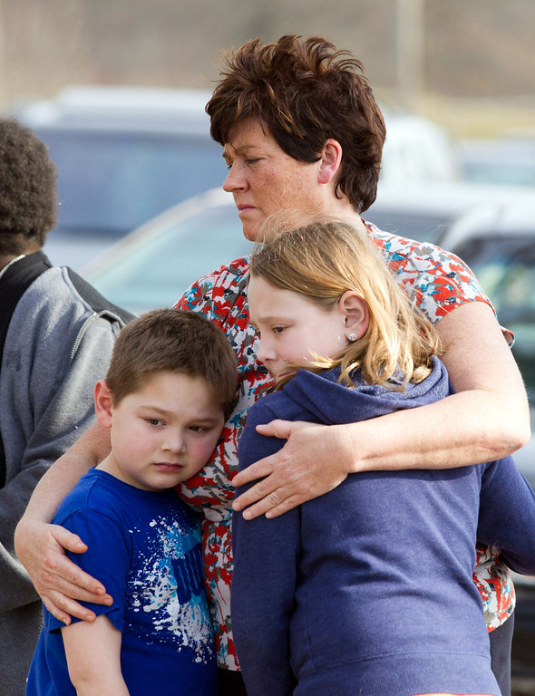 . An unidentified woman and her children visit the crash site that claimed the lives of six teens early in the morning on Park Ave. in Warren, Ohio on Sunday, March 10, 2013. (AP Photo/Scott R. Galvin)