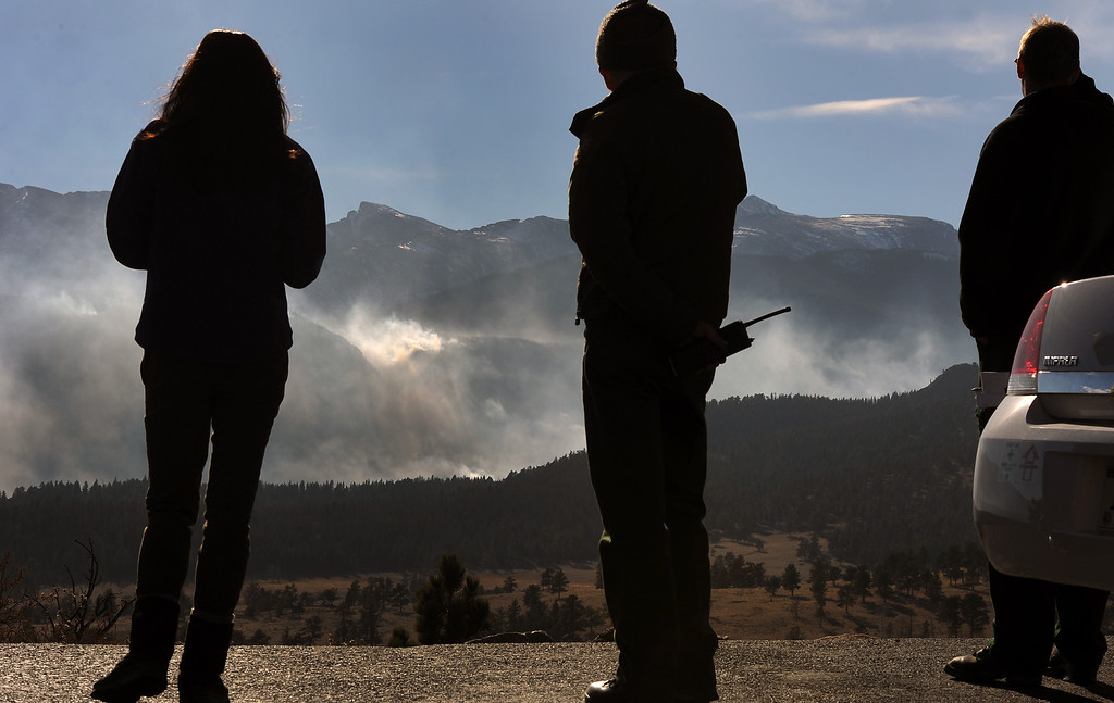 . Larry Frederick, middle, watches the Fern Lake Fire. Jake Brollier, another Public Information Officers on the Fern Lake Fire, is at right. Officials worry about winds kicking up later in the afternoon on December 2, 2012. The Fern Lake Fire, which has been burning in Rocky Mountain National Park since October, kicked up yesterday and forced the evacuation of hundreds of homes east of the fire. Helen H. Richardson, The Denver Post