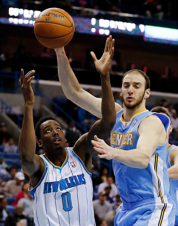 . New Orleans Hornets forward Al-Farouq Aminu (0) and Denver Nuggets center Kosta Koufos (41) reach for a loose ball in the first half of an NBA basketball game in New Orleans, Monday, March 25, 2013. (AP Photo/Bill Haber)