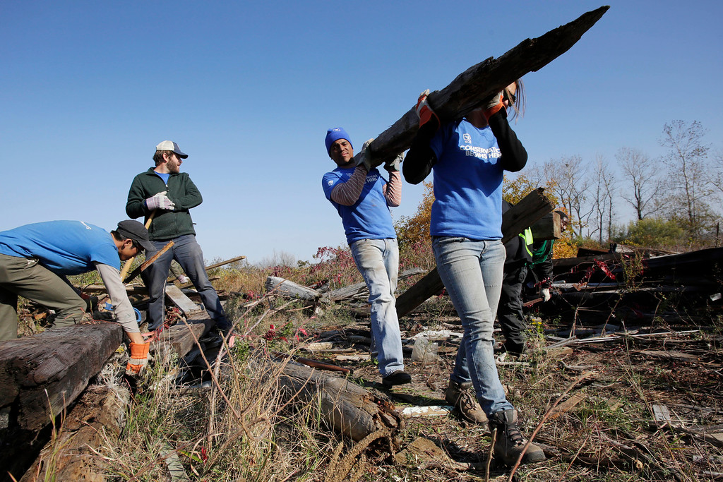 . Workers with the Student Conservation Association remove timbers and debris from marshland in the Gateway National Recreation Area in the Queens borough of New York, Tuesday, Oct. 29, 2013. A year ago Superstorm Sandy flooded the oceanside park, depositing tons of water-born debris. (AP Photo/Mark Lennihan)