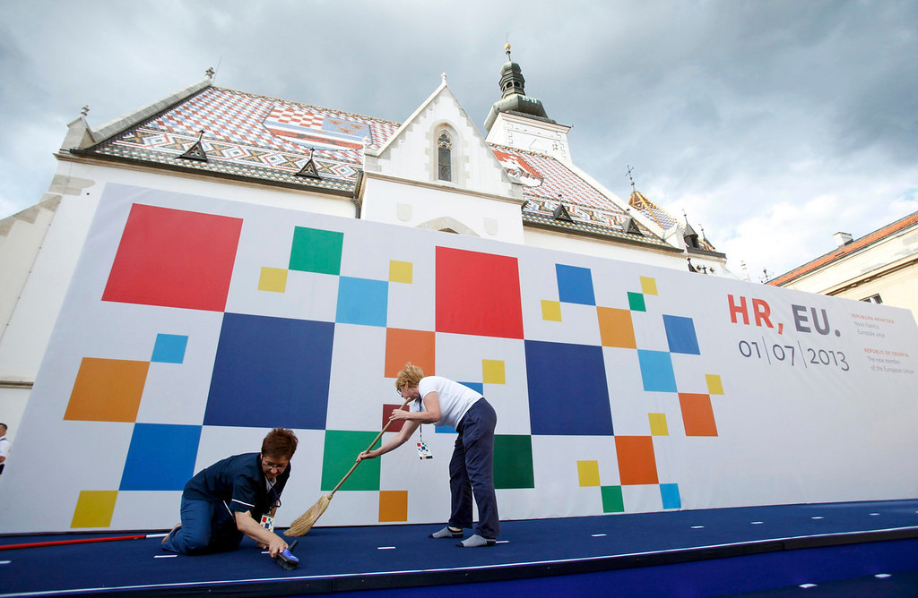 . Workers clean the podium prepared for the celebration of the accession of Croatia to the European Union at St. Mark\'s Square in Zagreb June 30, 2013. Croatia becomes the 28th member of the European Union at midnight, a milestone that caps the Adriatic republic\'s recovery from war but is tinged with anxiety over its weak economy and the state of the bloc it joins.  REUTERS/Antonio Bronic