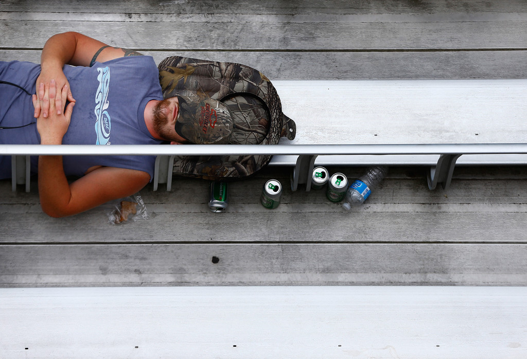. LOUDON, NH - JULY 13: A racing fan sleeps on the bleachers during the NASCAR Nationwide Series CNBC Prime\'s The Profit 200 at New Hampshire Motor Speedway on July 13, 2013 in Loudon, New Hampshire.  (Photo by Jared Wickerham/Getty Images)