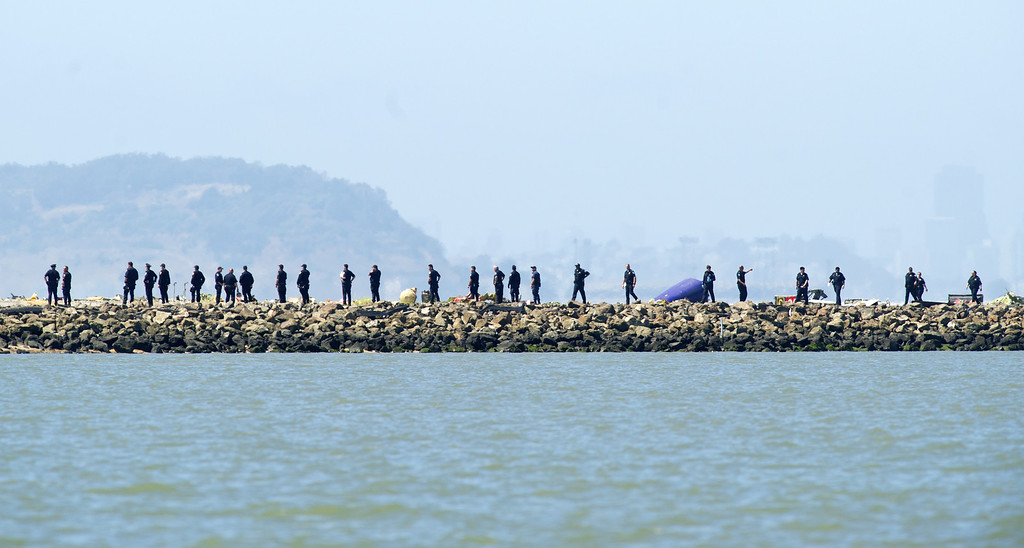 . Investigators comb the end of a San Francisco International Airport runway following the crash of Asiana Flight 214 on Saturday, July 6, 2013, in San Francisco. (AP Photo/Noah Berger)