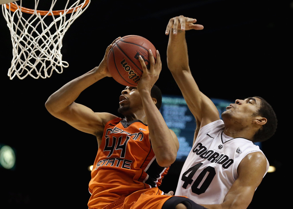 . LAS VEGAS, NV - MARCH 13:  Devon Collier #44 of the Oregon State Beavers drives to the basket past Josh Scott #40 of the Colorado Buffaloes for a layup in the second half during the first round of the Pac 12 Tournament at the MGM Grand Garden Arena on March 13, 2013 in Las Vegas, Nevada. Colorado defeated Oregon State 74-68.  (Photo by Jeff Gross/Getty Images)