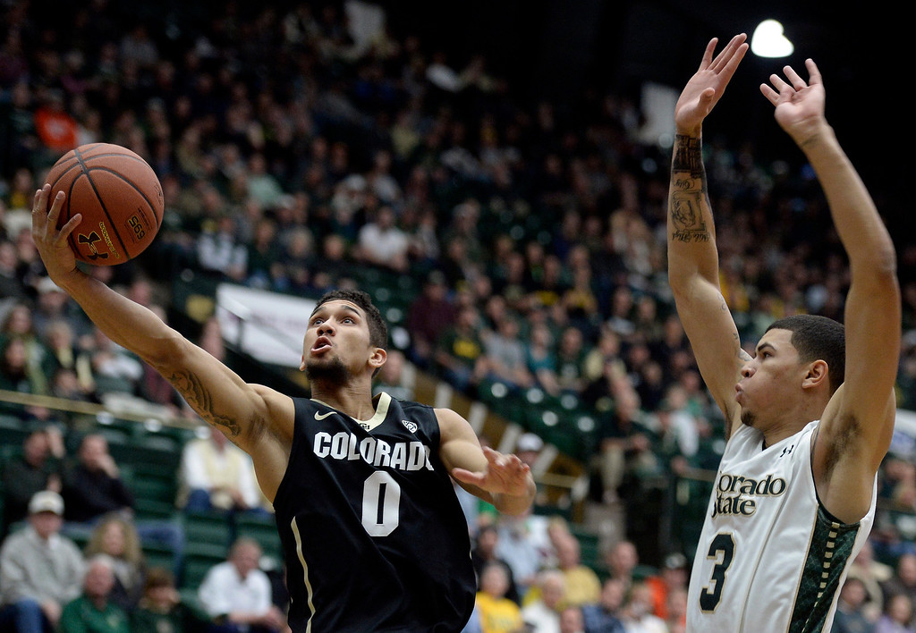 . University of Colorado\'s Askia Booker drives to the hoop in front of Marcus Holt during an NCAA game against Colorado State University on Tuesday, Dec. 3, 2013, at the Moby Arena in Fort Collins.