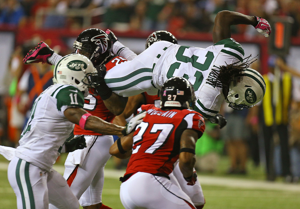 . New York Jets running back Chris Ivory goes up and over Atlanta Falcons safety William Moore (25) during the second half of an NFL football game Monday, Oct. 7, 2013, in Atlanta. The Jets won 30-28. (AP Photo/Atlanta Journal Constitution, Curtis Compton)